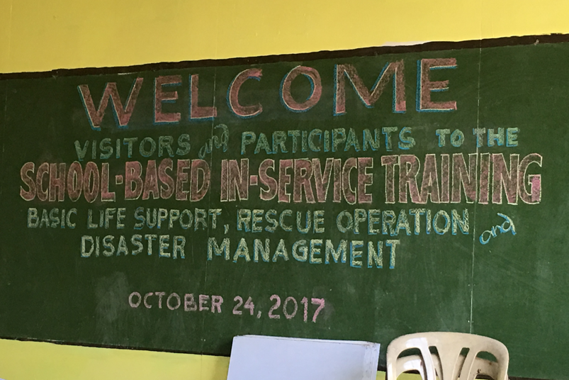 school blackboard displays disaster management training welcome message